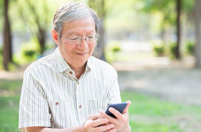 電話を見ながらプログレッシブレンズ眼鏡をかけている中年男性