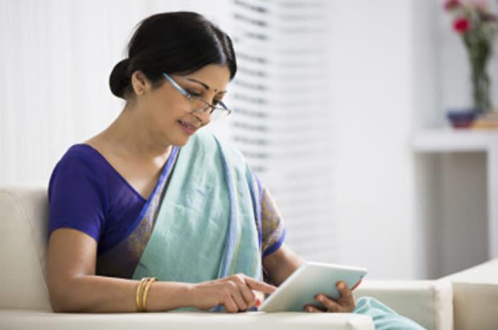 डिजिटल टैबलेट देख रही हिंदी महिला।
