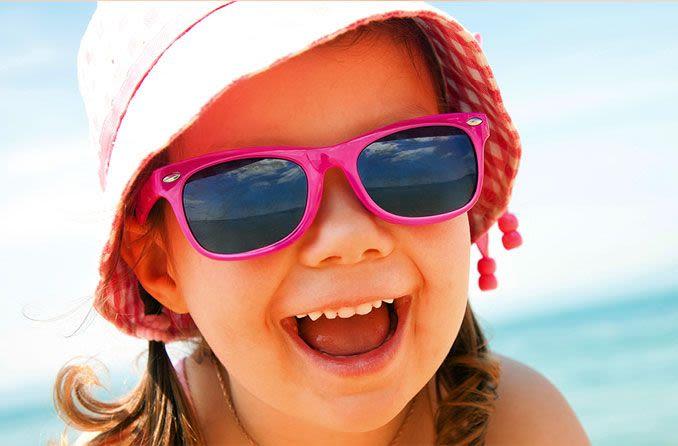 criança de óculos escuros e chapéu de sol na praia