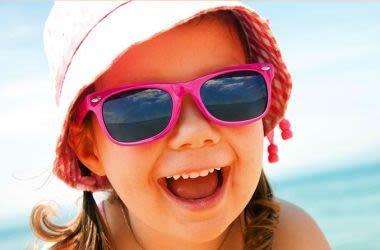 Enfant portant des lunettes de soleil et un chapeau de soleil à la plage.