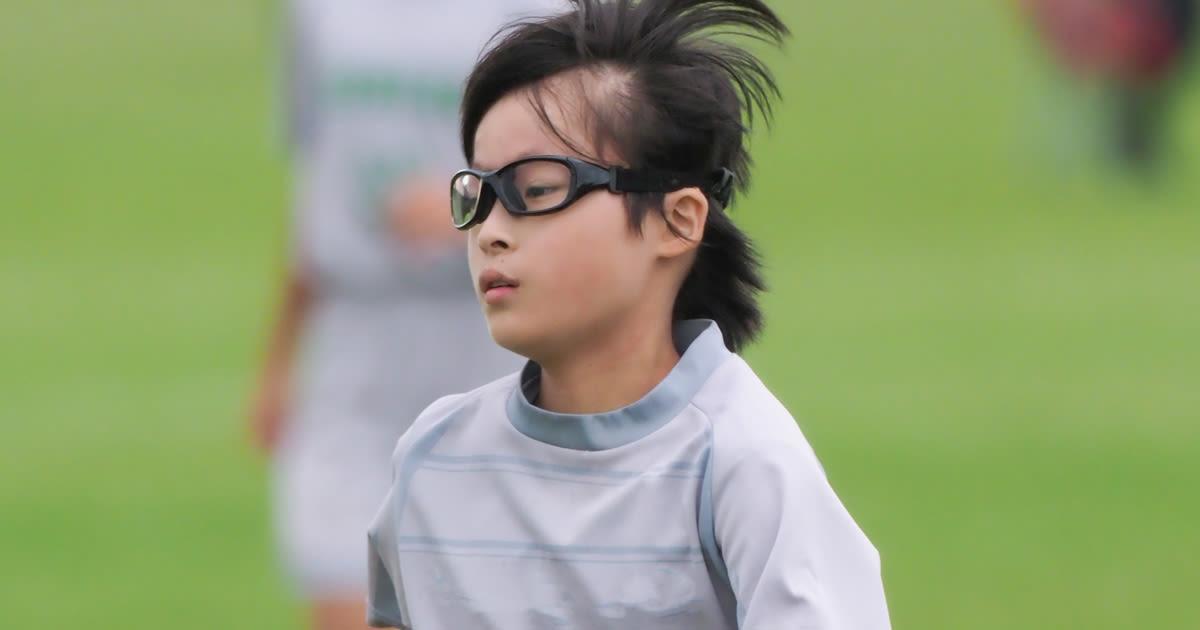 kid wearing sports eyewear while playing soccer
