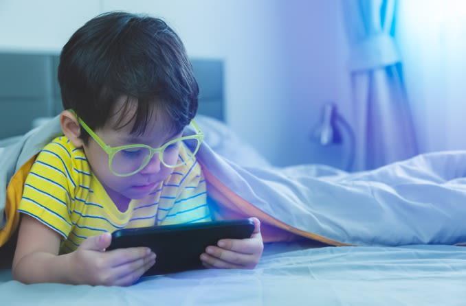 एक बच्चा जो नीले प्रकाश के चश्मे का उपयोग करता है