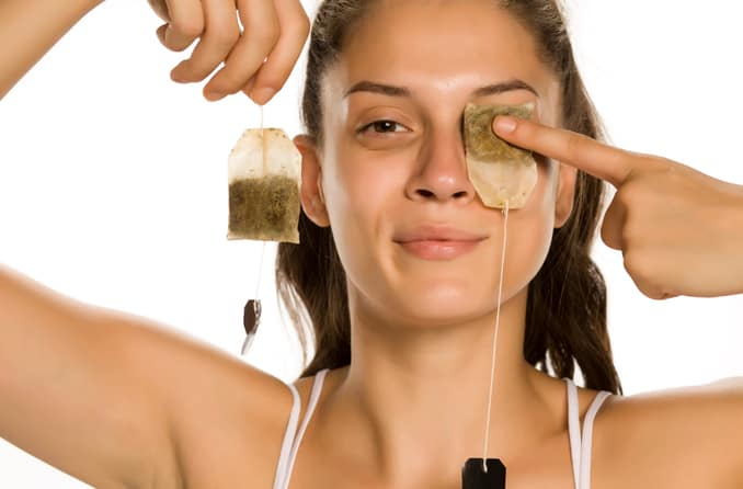 Woman using tea bags as cool compresses for her eyes