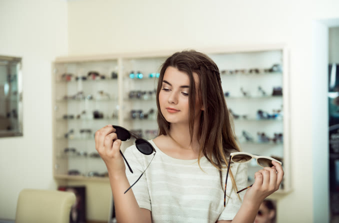 girl deciding between two pairs of sunglasses