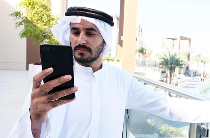 رجل ينظر إلى شاشة الهاتف دون نظارات للقراءة