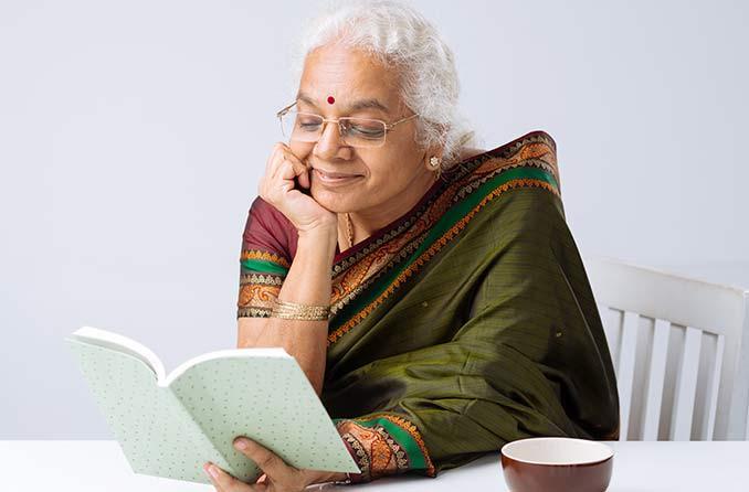 वरिष्ठ महिला पढ़ते हुए चश्मा पहनकर उपन्यास पढ़ती है