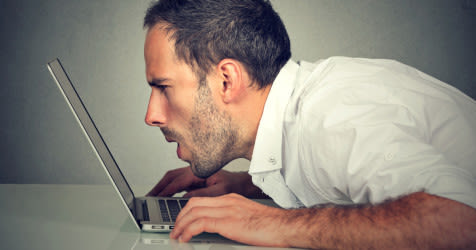 man squints at laptop screen without reading spectacles