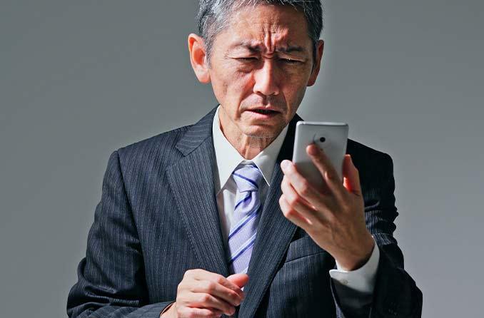 男は老眼鏡なしで電話の画面に目を細める