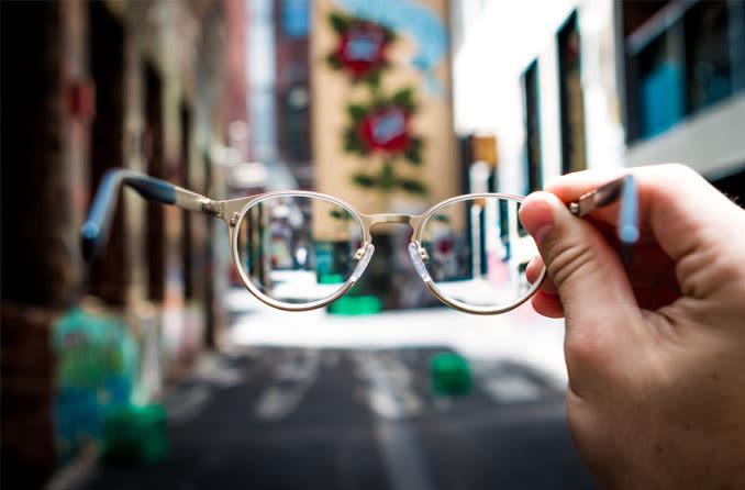 mão segurando um par de óculos