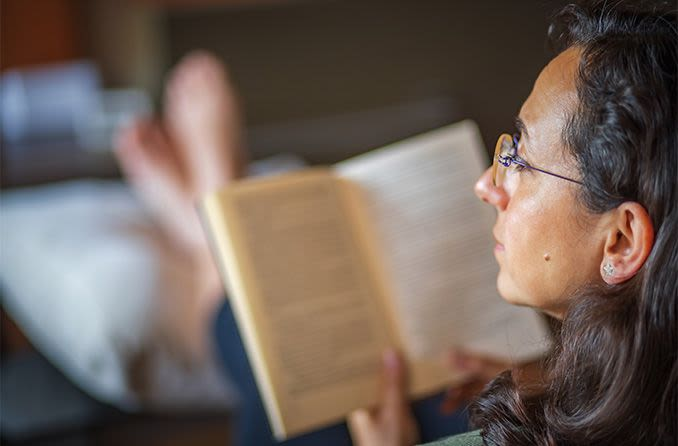 okuma gözlüğü takan bir kitap okuma kadın