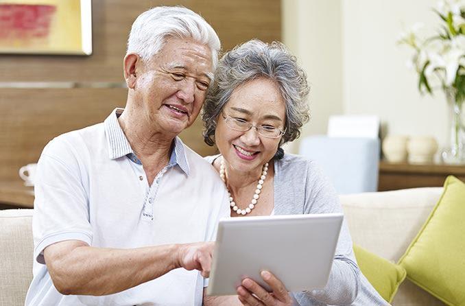 タブレットを見ている年配のカップル
