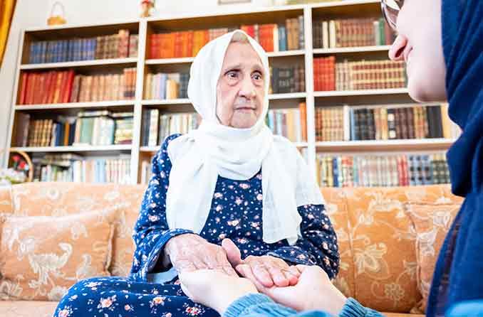 امرأة عجوز تمسك بيد حفيدتها
