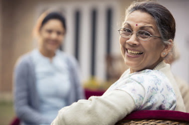 A happy older Indian woman wearing glasses smiling.
