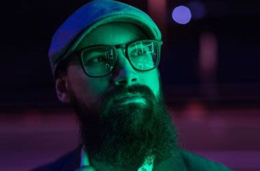 Bearded man wearing hat and glasses at night