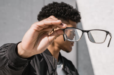 Teen boy removing glasses from face