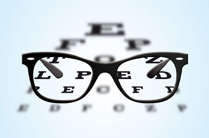 Black framed spectacles and an eye chart