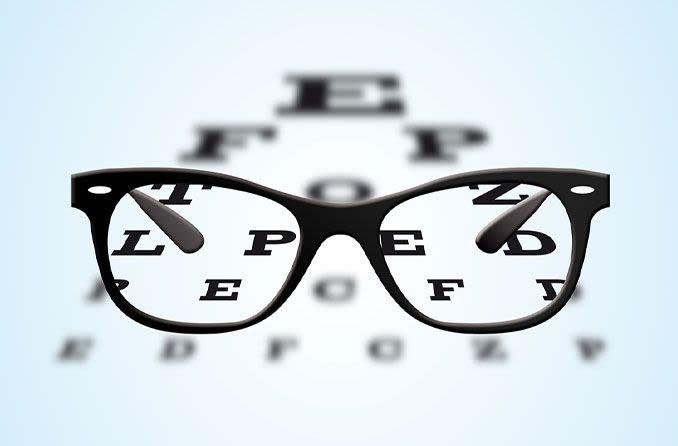 Brille mit schwarzem Rahmen, die auf einem augenärztlichen Sehtesttisch positioniert ist