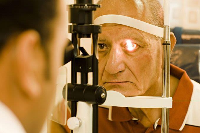 Um idoso recebendo um exame de vista