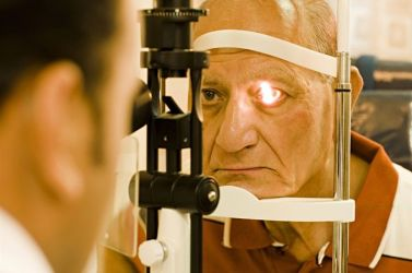 An elderly man receiving an eye exam