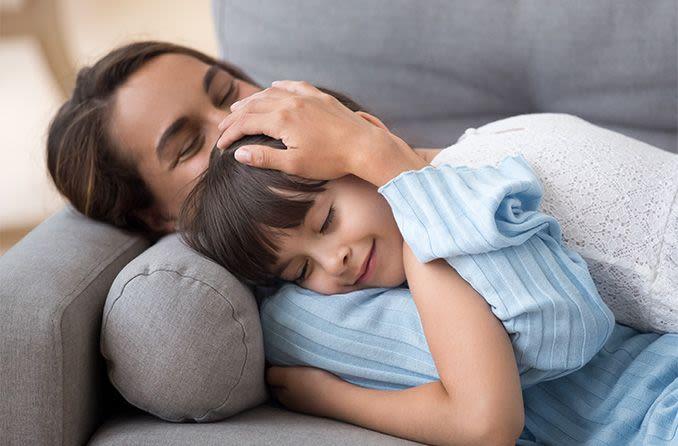 madre e hija descansando sus ojos en el sofá de casa