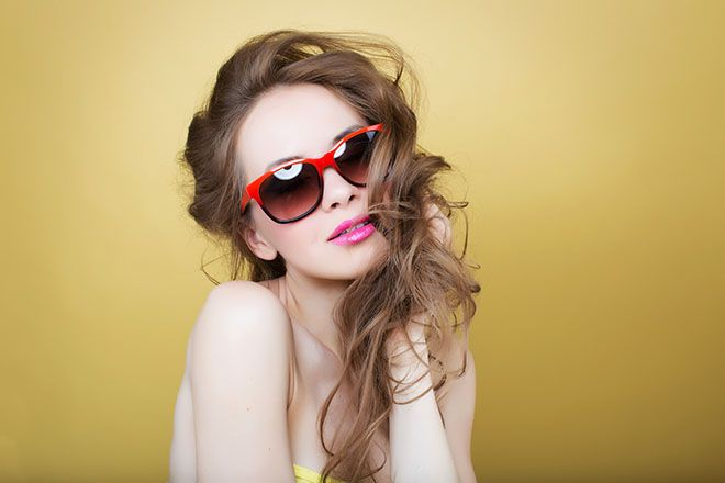 Woman wearing two toned sunglass frames on a yellow background