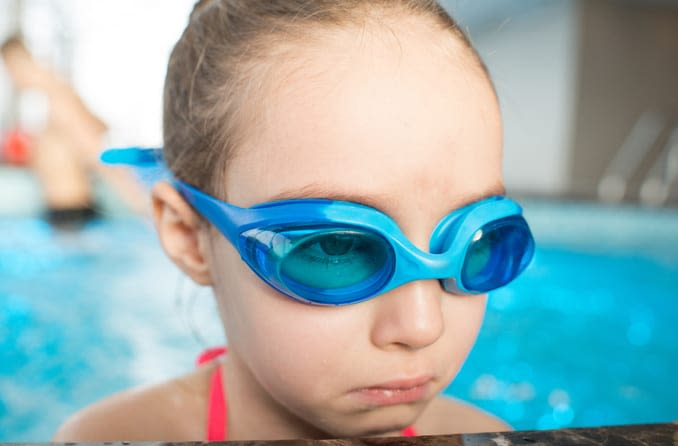 Little girl wearing swim goggles looks sad at the side of a pool