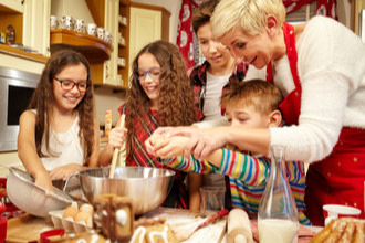Family cooking together for the holidays, includes two girls with glasses