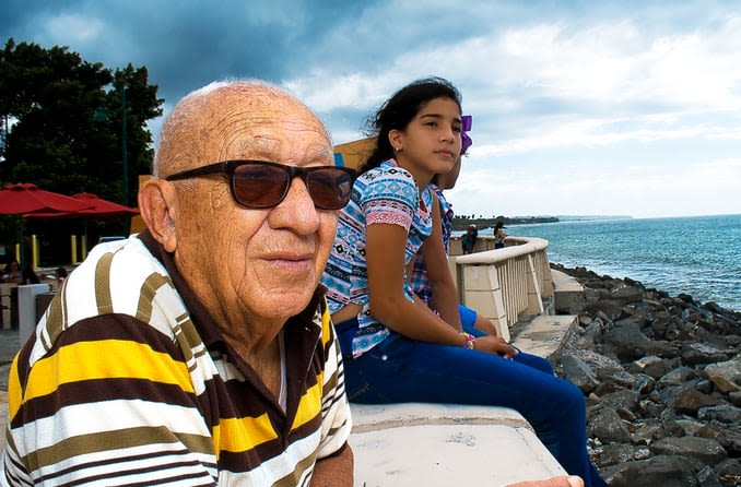 An older gentleman wears sunglasses while looking at the beach with his granddaughter