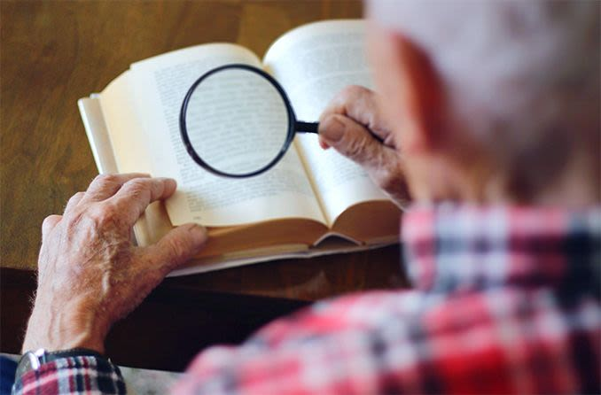 elderly man using low vision magnifier to read a book