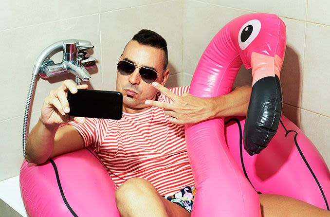 man wearing sunglasses in the tub taking a selfie