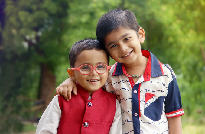 two kids, one wearing glasses