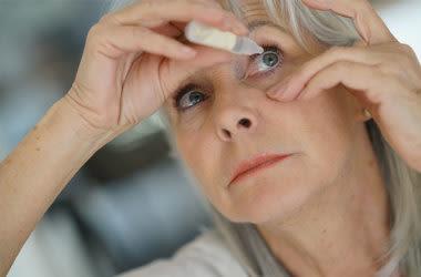 Frau, die Augentropfen für Glaukombehandlung verwendet