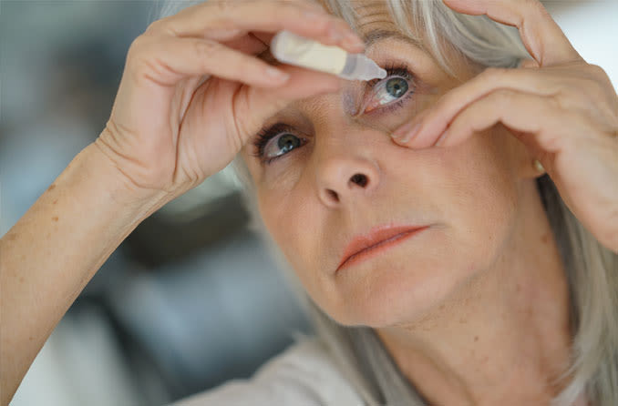 Woman using eye drops for glaucoma treatment