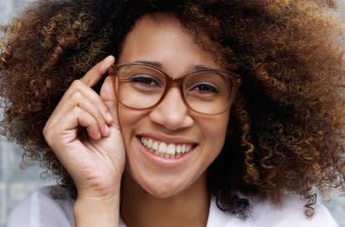 Lächelnde Frau freut sich über Ihre Brillengläser