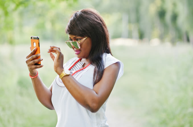 woman in sunglasses trying to see phone screen