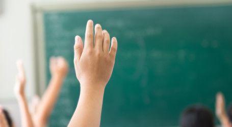 Manos de niños levantadas en clase