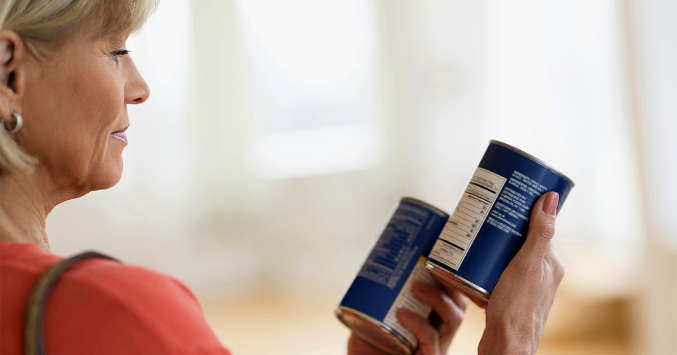 middle-age woman reading can labels without glasses