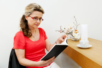 Woman over 40 wearing glasses and reading a book