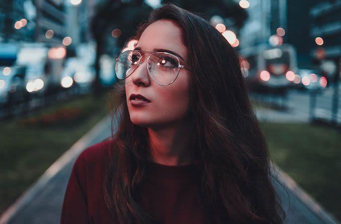 Женщина на улице, в очках, глядя вверх Zhenshchina na ulitse, v ochkakh, glyadya vverkh