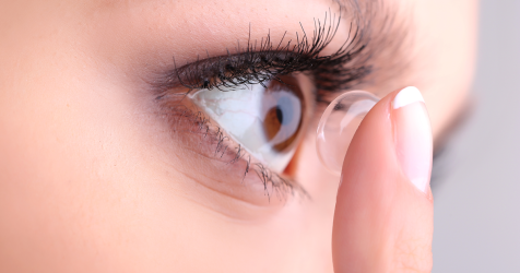 woman applying a contact lens