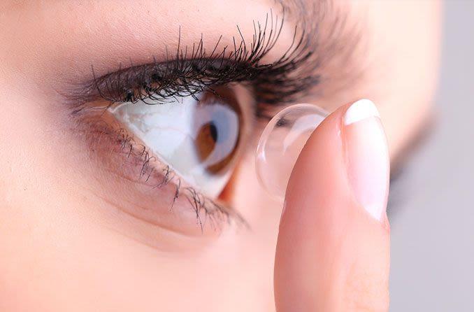Mulher aplicando uma lente de contato.