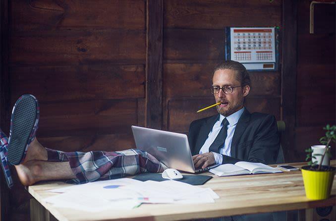 Hombre que trabaja desde casa vistiendo pantalones de pijama y chaqueta de traje de negocios