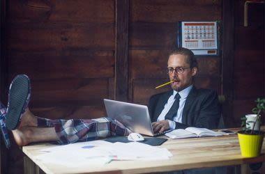 Mann, der von zu Hause aus arbeitet und Pyjamahosen und Business-Anzugjacke trägt