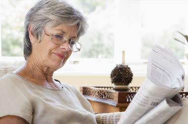 Mulher idosa lendo o jornal e usando óculos
