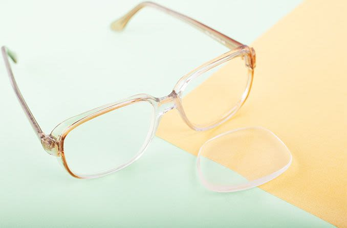 pair of eyeglasses with one lens popped out