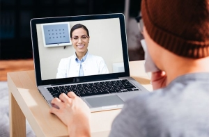 man talking with eye doctor on his laptop computer - telehealth
