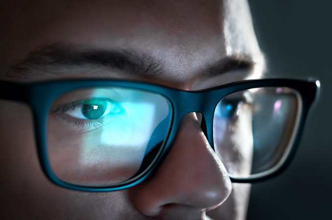 Man wearing computer glasses looking at a computer monitor - India