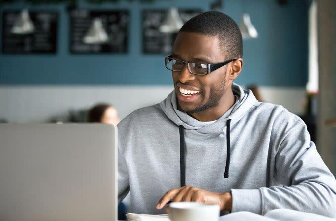 Hombre usando una laptop portando lentes para computadora