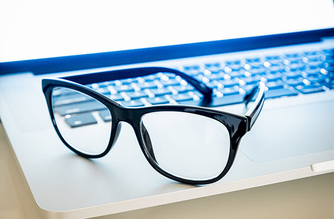 Pair of blue light eyeglasses sitting on a laptop