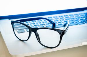 Pair of blue light eyeglasses sitting on a laptop